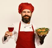 Man with beard on white background. Sommelier and cooking. Concept. Cook with smiling face in burgundy uniform holds baked dish and wine. Chef holds bowl with royalty free stock image