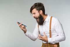 A young man a beard. A man with a beard in a white shirt and yellow suspenders shouts in the phone indignantly trying to explain his idea on gray background stock photo