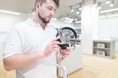 Man with a beard and a white T-shirt standing in the electronics store with headphones in and looking at the camera. Portrait of a man with a beard and a white T royalty free stock image