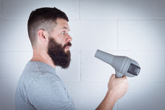 Man with beard. Man wipes his beard with hair dryer Royalty Free Stock Photo