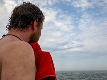 A man with a beard wipes off a towel after swimming in the sea.back view royalty free stock photography