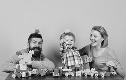 Man with beard, woman and boy play on pink background. Mom, dad and kid in playroom. Childhood and playing concept. Family with happy faces build toy cars out royalty free stock images