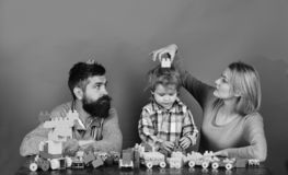Man with beard, woman and boy play on red background. Family with serious faces build toy cars out of colored construction blocks. Mom, dad and kid in playroom stock photos