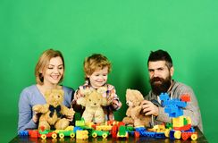 Man with beard, woman and boy play on green background. Man with beard, women and boy play on green background. Parenthood and game concept. Mom, dad and kid in stock photo