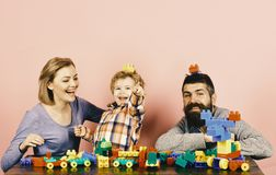 Man with beard, woman and boy play on pink background. Man with beard, women and boy play on pink background. Mom, dad and kid in playroom. Childhood and playing stock image