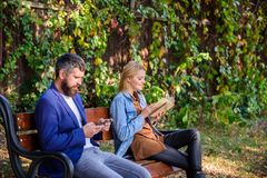 Man with beard and woman read alternative information storage. Read book in park pleasant leisure. Interesting. Man with beard and women read alternative royalty free stock photography