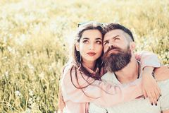 Man with beard and woman sits on grass spring day. Spring leisure concept. Couple on happy dreamy faces sitting at. Man with beard and women sits on grass spring stock image