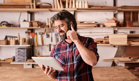 Man with beard in woodwork studio using phone and tablet. Smiling man with a rugged beard, talking on his mobile phone while looking at a digital tablet in his stock images