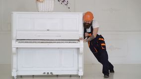 Man with beard worker in helmet and overalls pushes, efforts to move piano. Loader moves piano instrument. Man with. Beard, worker in overalls and helmet fall stock video