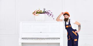 Man with beard, worker in overalls and helmet lean on piano, white background. Courier delivers furniture in case of royalty free stock photo