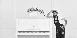 Man with beard, worker in overalls and helmet lean on piano, white background. Courier delivers furniture in case of stock photo