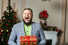 Man with beard yawning and holding a box Royalty Free Stock Images