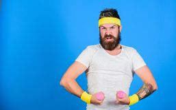 Man bearded athlete exercising dumbbell. If you want to be strong. Motivated athlete guy. Join my sport class. Sportsman. Retro outfit training blue background stock image
