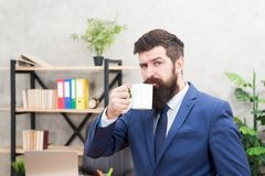 Man bearded businessman hold coffee cup stand office background. Start day with coffee. Successful people drink coffee stock photos