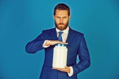 Man or bearded businessman with plastic jar on blue background. Man or bearded businessman with plastic jar in formal outfit on blue background, copy space stock images