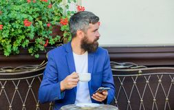 Man bearded businessman sit terrace with smartphone and cup of coffee. Take care of business even while enjoy coffee royalty free stock images