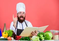 Man bearded chef cooking food. Culinary arts concept. Amateur cook read book recipes. Man learn recipe. Try something. New. Cookery on my mind. Improve cooking royalty free stock photo