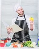 Man bearded chef cooking food. Guy read book recipes. Culinary arts concept. Man learn recipe. Improve cooking skill stock image