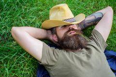 Man bearded cowboy lay on grass relaxing or having nap. Cowboy relaxing at green meadow. Brutal cowboy with green. Spikelet in mouth. Hipster tourist find Royalty Free Stock Photo