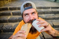 Man bearded eat tasty sausage. Urban lifestyle nutrition. Junk food. Carefree hipster eat junk food while sit stairs. Guy eating hot dog. Snack for good mood royalty free stock images