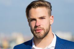 Man with bearded face on sunny outdoor. Businessman with stylish haircut on blurred sky. Business fashion, style and trend. Groomi. Ng and hair care in royalty free stock image