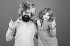 Man bearded father and girl wear colorful wig while eat lollipop candy. Thing loving father do for children. Tribute to stock image
