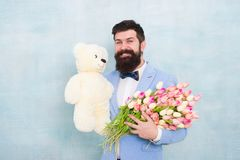 Man bearded gentleman suit bow tie hold teddy bear and bouquet. Happy and in love. Gentleman making romantic surprise
