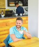 Man bearded guy drinks cappuccino wooden table cafe. Cafe visitor happy smiling face enjoy coffee drink. Improve overall royalty free stock photos