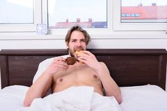 Man bearded handsome guy eating breakfast in bed. French breakfast stereotype. Man eats croissant and drinking coffee. Guy having coffee and holds croissant Stock Photos