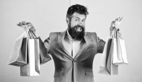 Man bearded hipster businessman formal suit carry paper shopping bags. Ready for holiday. Buy gifts for everyone. Buy. Gifts in advance. Enjoy shopping black royalty free stock photo