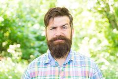 Man bearded hipster green trees background. Guy relax in summer nature. Eco lifestyle. United with environment. Handsome stock images