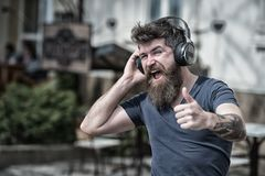 Man bearded hipster with headphones listening music. Hipster enjoy high quality sound of song in headphones. Get music. Subscription. Excellent music in his stock photo