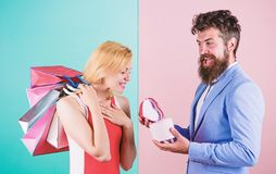 Man bearded hipster hold gift box and girl enjoy shopping. Ask man to purchase lots presents for girlfriend. Couple with stock photo