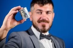 Man bearded hipster hold rolled dollars banknotes. Guy formal suit offer bribe or purchase. Easy money concept. Rich. Businessman hold rolled money. Hipster stock photo