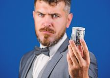 Man bearded hipster hold rolled dollars banknotes. Guy formal suit offer bribe or purchase. Hipster offer money blue. Background close up. Easy money concept royalty free stock photo