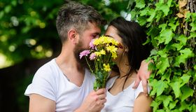 Man bearded hipster kisses girlfriend. Couple love romantic date nature background. Love romantic feelings. Couple in. Love hiding behind bouquet flowers kiss stock photography