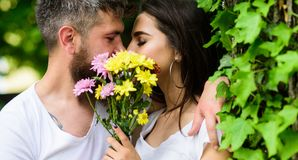 Man bearded hipster kisses girlfriend. Secret romantic kiss. Love romantic feelings. Moment of intimacy. Couple in love. Hiding behind bouquet flowers kiss stock image