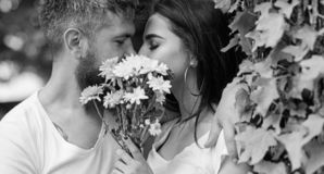 Man bearded hipster kisses girlfriend. Secret romantic kiss. Love romantic feelings. Moment of intimacy. Couple in love. Hiding behind bouquet flowers kiss stock photography