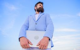 Man bearded hipster manager hold laptop blue sky background. Top qualities of excellent manager. Manager with laptop. Modern communications. Guy formal suit stock photography