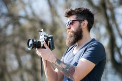 Man bearded hipster photographer hold vintage camera. Photographer with beard and mustache amateur photographer nature. Background. Man with long beard busy stock photo