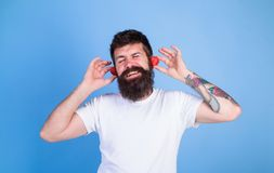Man bearded hipster red ripe strawberry ears as headphones. Summer hit concept. Hipster beard listen music strawberry. Earphones. Summer playlist music. Guy Royalty Free Stock Photos