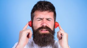 Man bearded hipster red ripe strawberry ears as headphones. Summer hit concept. Summer playlist music. Guy enjoy juicy. Sound summer hit song music. Hipster Stock Photography