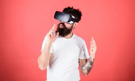 Man bearded hipster with virtual reality headset on red background. Shooting VR game. First person shooter shows how stock photos