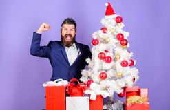 Man bearded hipster wear formal suit near christmas tree. Christmas gifts and decorations. How to organize awesome. Office christmas party. Ready to celebrate stock photography