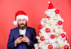 Man bearded hipster wear formal suit and santa hat hold smartphone. Send christmas greeting mobile message. Short. Christmas wishes. Manager congratulate stock photography