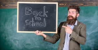 Man bearded holds blackboard inscription back to school. Back to school teachers recruitment. Looking committed teacher