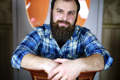 Man bearded look. Bearded handsome man sitting on a chair and posing for the camera Stock Photography