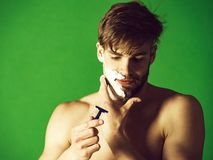 Man shaving beard hair with safety razor and foam. Man or bearded macho with naked shoulders shaving beard hair with safety razor and white foam or cream on face stock images