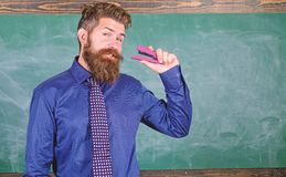 Man bearded teacher or educator in formal wear holds stapler chalkboard background. School supplies and stationery. Use. Stapler safely. Be careful with stock image