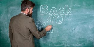 Man bearded teacher missed his work during vacation. Teacher near chalkboard holds chalk write inscription back to. School. Back to school concept. Teacher royalty free stock photo